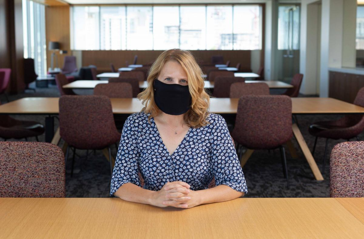 Staff member at a desk with protective face covering, photo